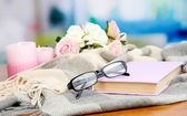 Composition with old book, eye glasses, candles, flowers and plaid on bright background