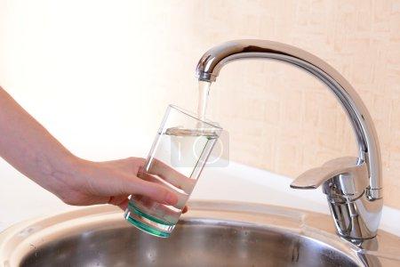 Photo pour Verre à main d'eau versé du robinet de cuisine - image libre de droit