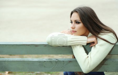 Photo for Young lonely woman on bench in park - Royalty Free Image