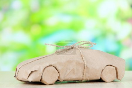 Car wrapped in brown kraft paper, on nature background