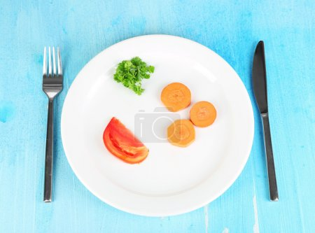 Photo for Small portion of food on big plate on wooden table close-up - Royalty Free Image
