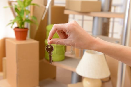 Photo for Female hand with keys ob stack of cartons background: moving house concept - Royalty Free Image