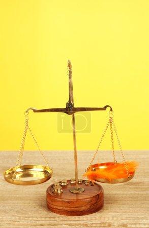 Waage mit Feder auf Tisch auf gelbem Hintergrund