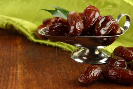 Dried dates in metal dish with napkin on wooden background