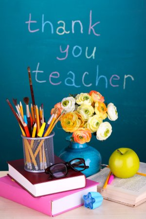 School supplies and flowers on blackboard background with inscription Thank you teacher