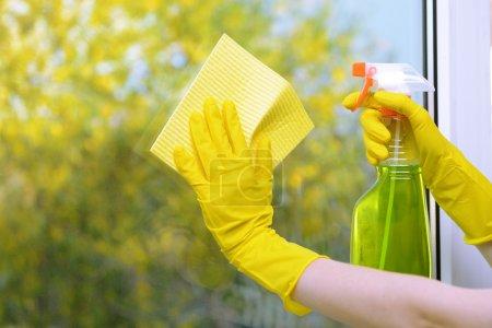 Photo pour Mains avec le spray de nettoyage de la fenêtre - image libre de droit