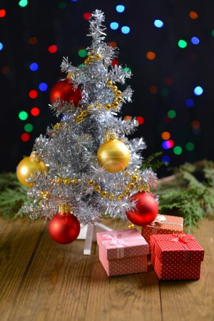 Decorative Christmas tree with gifts on table on bright background