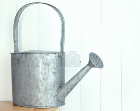 Watering can on wooden background