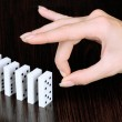Hand pushing dominoes on wooden background...