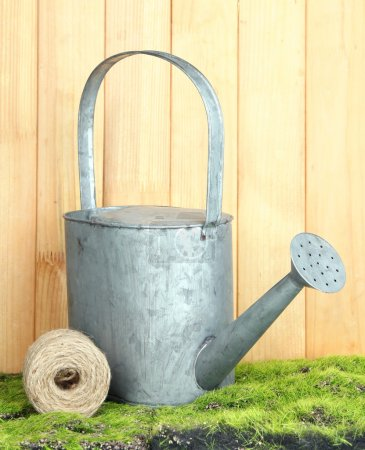 Watering can on grass on wooden background