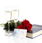 Wedding rings on bible with roses and glasses of champagne isolated on white