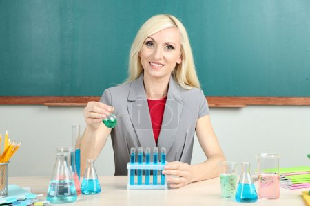 Chemistry teacher with tubes sitting at table on blackboard background