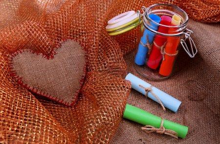 Photo pour Rêves écrits le couleur roulé papier en pot de verre, sur fond d'un sac et le tissu - image libre de droit