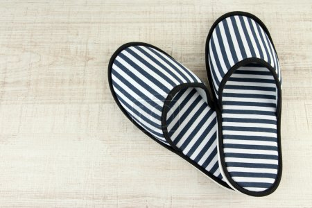 Striped slippers on wooden background