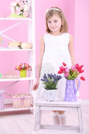 Beautiful little girl and stand with flowers on pink background