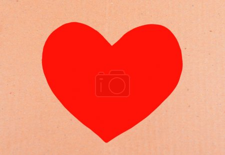 Cardboard heart on red background