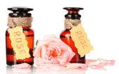 Lahve z ropy a rose izolovaných na bílém