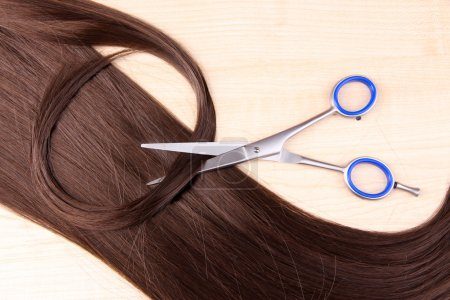 Long brown hair and scissors on wooden background...