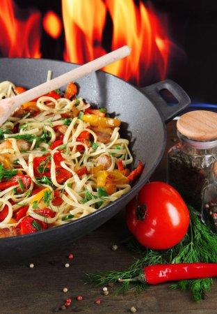 Photo pour Nouilles aux légumes sur wok sur fond de feu - image libre de droit