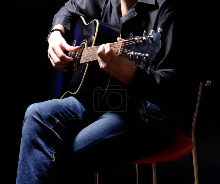 Photo for Young musician playing acoustic guitar and singing, on dark background - Royalty Free Image