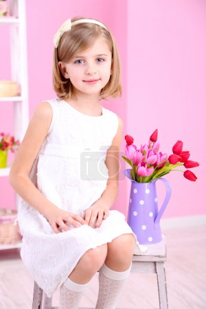 Photo for Little girl sitting on small ladder with flowers on pink background - Royalty Free Image