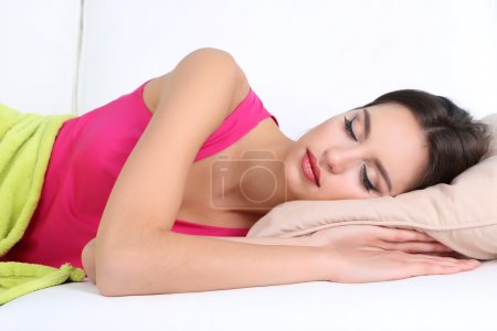 Beautiful young woman sleeping on sofa close up