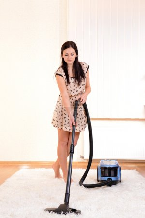 Beautiful young woman with vacuum cleaner in room