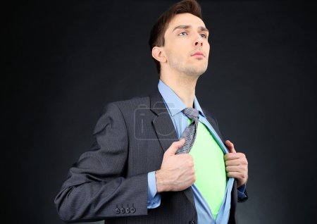 Young business man tearing apart his shirt revealing superhero suit, on dark background