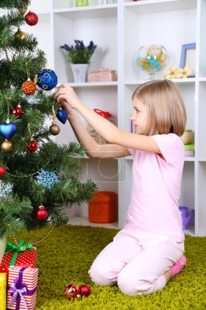 Little girl decorating Christmas tree in room
