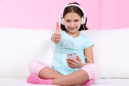 Beautiful little girl sitting on sofa and listening to music, on home interior background