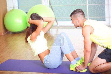 Photo pour Fille et formateur engagé dans la salle de fitness - image libre de droit