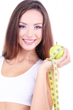 Beautiful young woman with green apple and measuring tape isolated on white