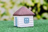 Malý domek na zelené trávě, na světlé pozadí