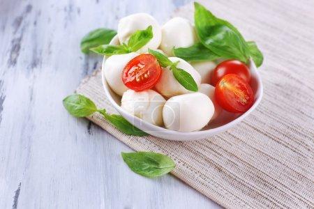 schmackhafter Mozzarella-Käse mit Basilikum und Tomaten in Schüssel, auf Holztisch