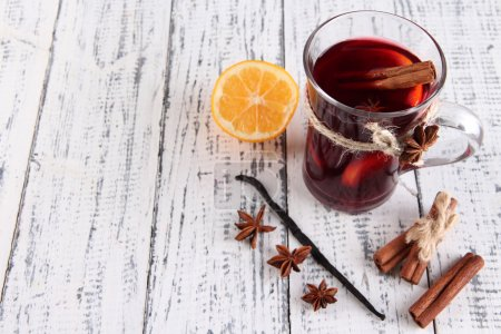 Mulled wine with lemon and spices on wooden background