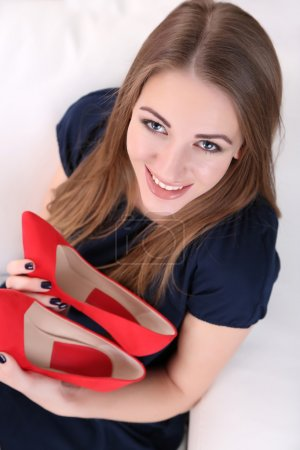 Girl sitting on sofa with sexy red shoes, on home ...