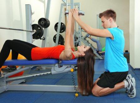 Photo pour Jeune entraîneur et femme engagée avec des haltères dans la salle de gym - image libre de droit