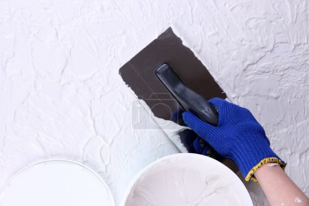 Construction trowel and worker hands on wall with textured plaster