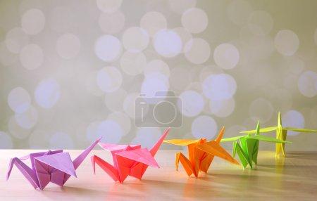 Foto de Grullas de origami en mesa de madera, sobre fondo claro - Imagen libre de derechos