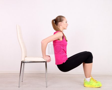 Young beautiful fitness girl exercising with chair in gym