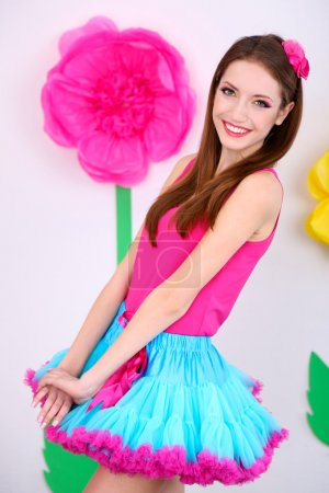 Beautiful young woman in petty skirt on decorative background