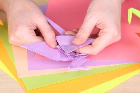 Foto de Cerrar las manos haciendo origami grúa, - Imagen libre de derechos