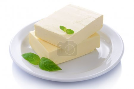Tasty butter on plate isolated on white