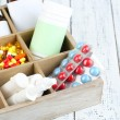 Medical pills, ampules in wooden box, on color bac...
