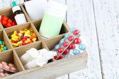 Lékařské tablety, ampule v dřevěné krabici, na barvu pozadí