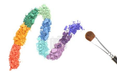 Rainbow crushed eyeshadow and professional make-up brush isolated on white