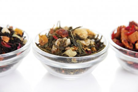 Different kinds of dry tea in bowls isolated on wh...