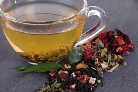 Photo pour Tasse de thé avec thé sec aromatique sur fond en bois - image libre de droit