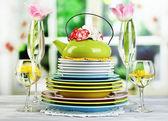 Zásobník barevné keramické talíře a květiny, na dřevěný stůl, na světlé pozadí