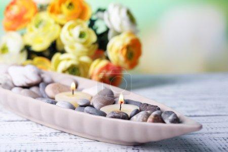 Photo pour Composition avec pierres de spa, des bougies et des fleurs sur la table en bois de couleur, sur fond clair - image libre de droit